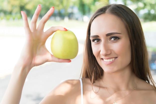 Ragazza a dieta soleggiata all'aperto. sport e salute. mela verde della stretta della donna. attività ed energia estive. frutta e vitamina.