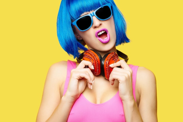 Ragazza dj in occhiali da sole parrucca e costume da bagno rosa ascoltando musica in cuffia su sfondo giallo. foto di alta qualità