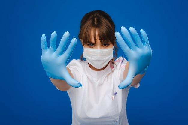 Una dottoressa sta in una maschera medica, isolata su uno sfondo blu.