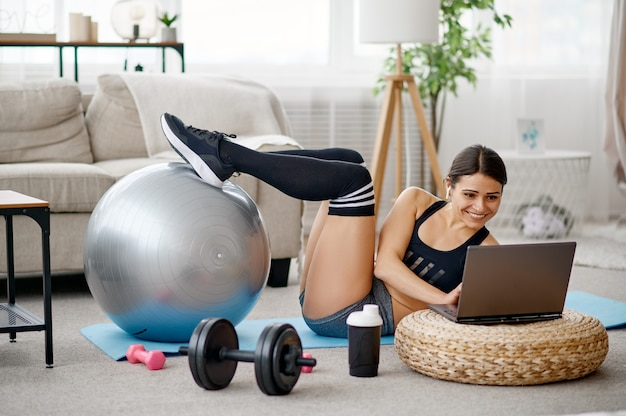 Ragazza che fa esercizio con la palla, formazione online di pilates al computer portatile. persona di sesso femminile in abbigliamento sportivo, allenamento sportivo internet, interno della stanza