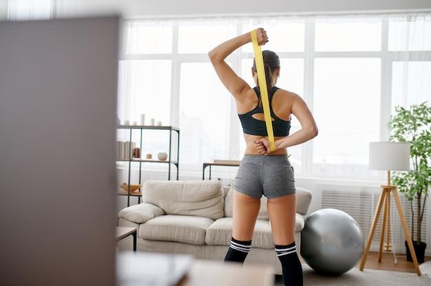 Ragazza che fa esercizio con la gomma, allenamento fitness online al computer portatile. persona di sesso femminile in abbigliamento sportivo, allenamento sportivo internet, interno della stanza