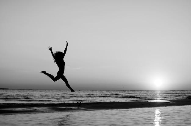 Ragazza che fa ginnastica sulla spiaggia al tramonto