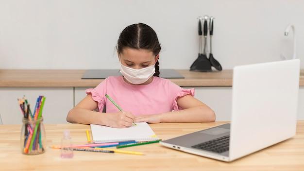 Ragazza che fa i compiti con la maschera