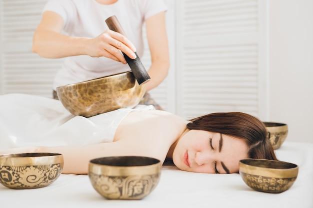 Ragazza che fa le ciotole di canto di terapia di massaggio nella stazione termale