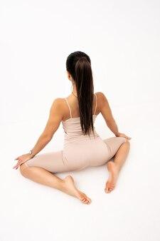 Ragazza che fa stretching in studio su sfondo bianco. una bella ginnasta con un corpo flessibile e un'uniforme atletica.