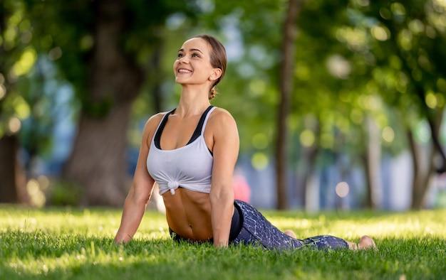 Ragazza che fa yoga in natura e in piedi nella posa del cane verso l'alto con un sorriso. giovane donna che si esercita e si stira in estate