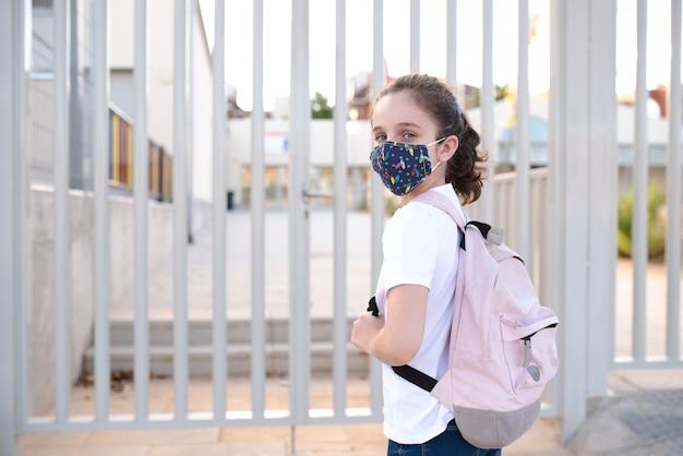 Ragazza alla porta della scuola con la maschera nella nuova normalità