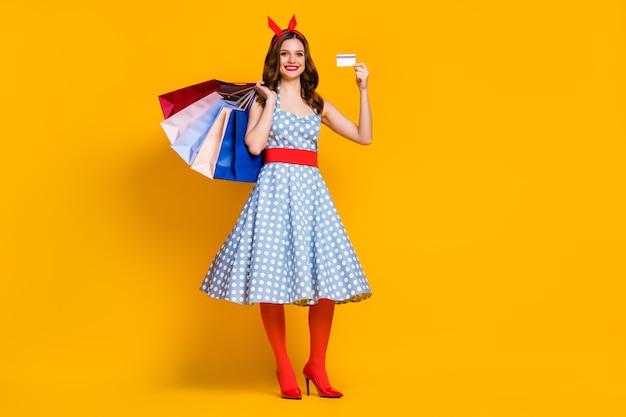 La ragazza in vestito punteggiato tiene i sacchetti della spesa e la carta di credito