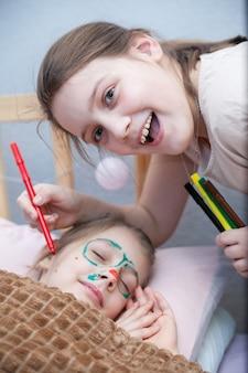 Ragazza che disegna i baffi sulla faccia della sua sorella addormentata. primo d'aprile