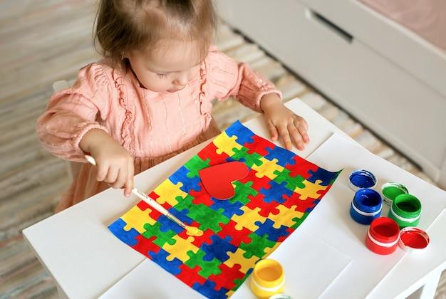 Una ragazza disegna un disegno da un puzzle colorato per il giorno della giornata mondiale dell'autismo