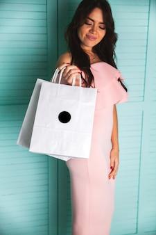 Ragazza che sogna di fare shopping. sorridente donna elegante in abito rosa e con le borse della spesa
