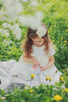 Ragazza in vestito che tiene il libro blu nel giardino di ciliegio di primavera