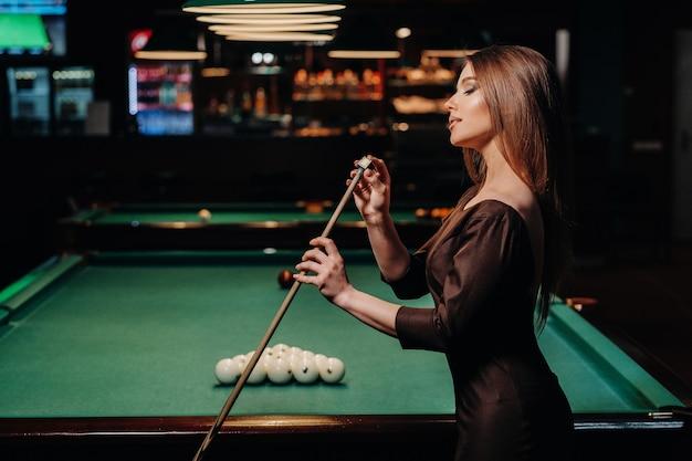 Una ragazza in un vestito sta con una stecca in mano e la pulisce con il gesso in un club di biliardo con le palle in mano.
