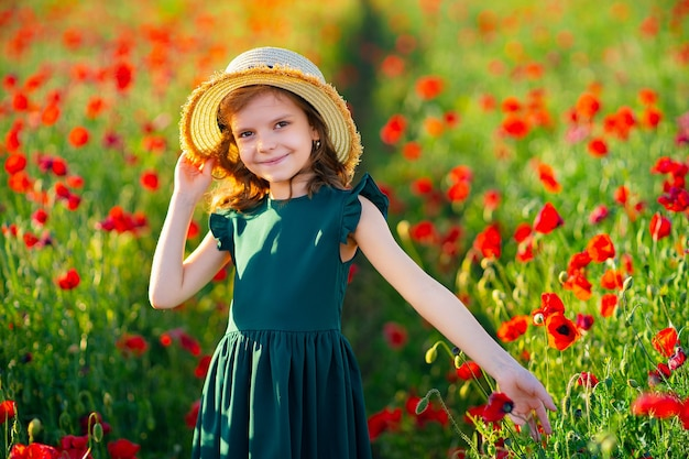 Ragazza in vestito e cappello di paglia all'aperto al campo di papaveri