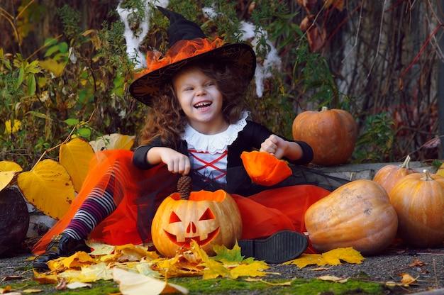 Una ragazza vestita come una piccola strega con una gonna arancione e un cappello nero a punta siede accanto a zucche di halloween in un parco in autunno