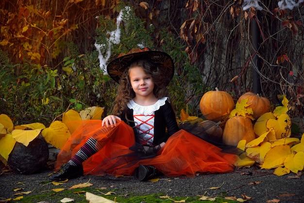 Una ragazza vestita come una piccola strega con una gonna arancione e un cappello nero a punta con una scopa in un parco di halloween in autunno con una zucca