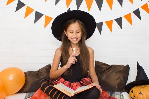 Una ragazza vestita da strega tiene in mano un lecca-lecca e guarda in un libro festeggia halloween