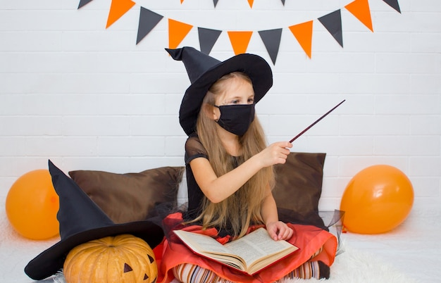 Una ragazza vestita da strega con un libro di uno stregone con una bacchetta magica evoca incantesimi