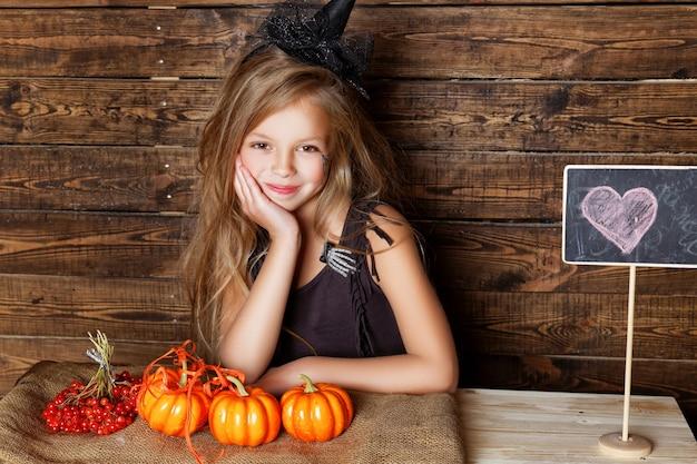 Una ragazza vestita da strega con decorazioni di halloween