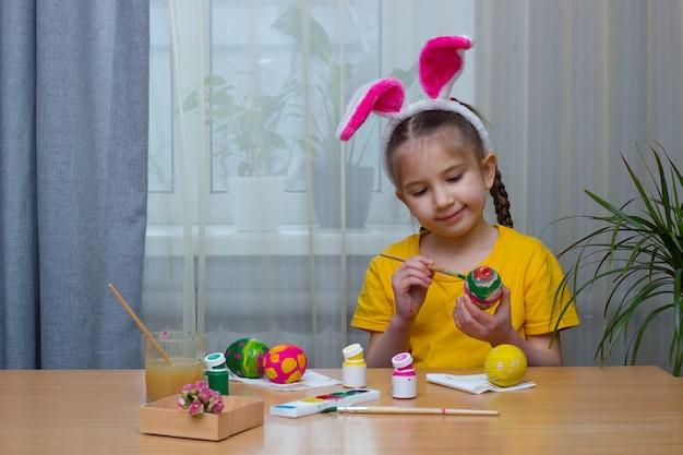 La ragazza vestita con orecchie da coniglio si siede al tavolo di casa decora le uova per le vacanze di pasqua easter