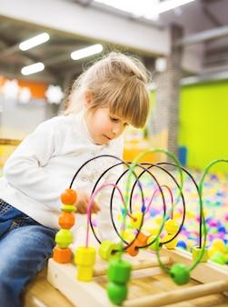 Una ragazza vestita in jeans e un maglione bianco sta giocando con un giocattolo di legno in via di sviluppo nella stanza dei giochi