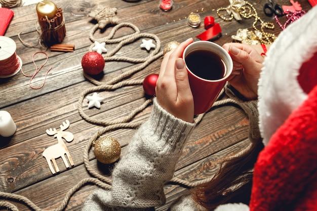 La ragazza beve il tè caldo al tavolo di legno con accessori natalizi
