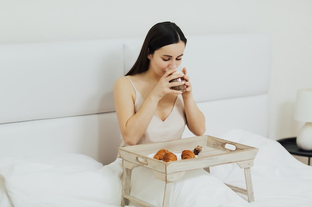 Ragazza che beve cappuccino e mangiare la colazione sul letto al mattino