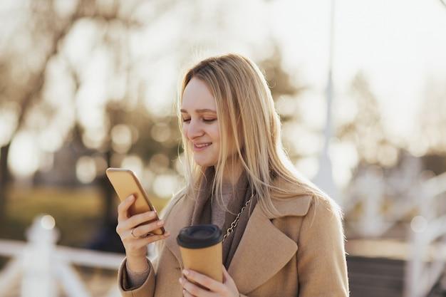 Ragazza che beve caffè per strada e utilizza il telefono
