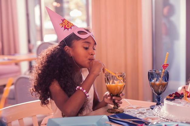 Ragazza che beve succo di frutta a una festa di compleanno