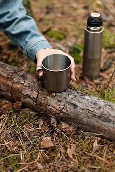 Una ragazza che beve il tè da un thermos. tè del thermos nel bosco. bere dal thermos. l'atmosfera della foresta.