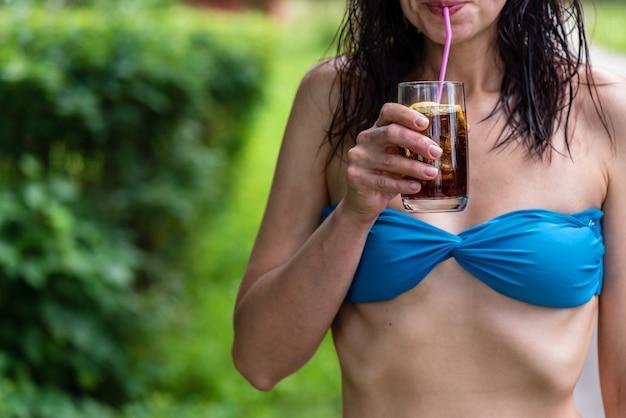 Una ragazza beve un cocktail all'aperto