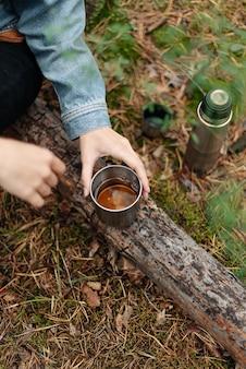 La ragazza beve tè profumato da un thermos seduto su un tronco. tè di un thermos nella foresta. bevo da un thermos. atmosfera della foresta.