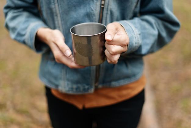 La ragazza beve tè profumato da un thermos. tè di un thermos nella foresta. una ragazza con una giacca di jeans a un picnic. atmosfera della foresta.