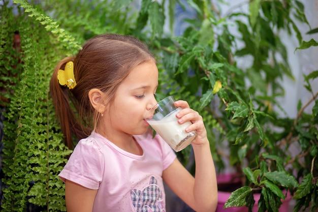 La ragazza beve il kefir da un vetro trasparente a casa. una corretta alimentazione per il bambino
