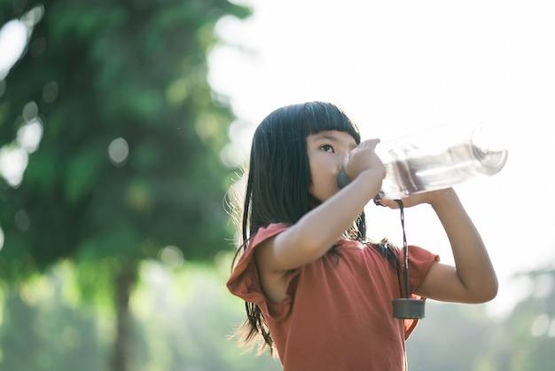 La ragazza beve acqua da una bottiglia dopo l'allenamento