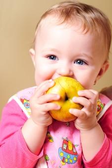 Ragazza che mangia una mela e sorridente