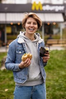 Ragazza che mangia un hamburger con fast food
