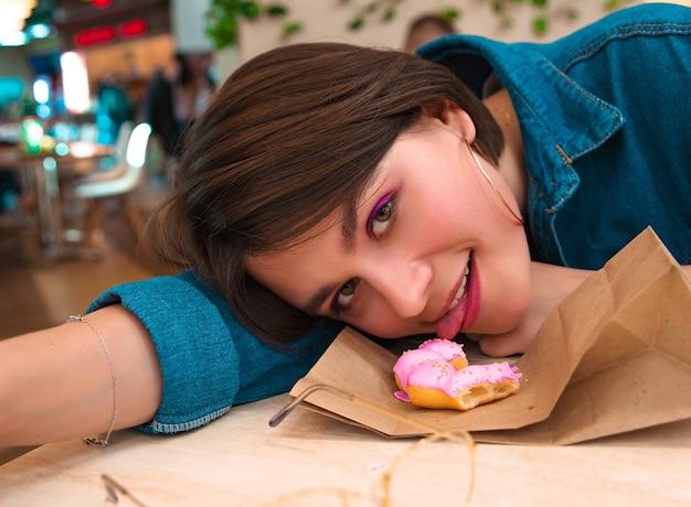 Ragazza che mangia una ciambella al centro commerciale, lingua, ciambella, quad