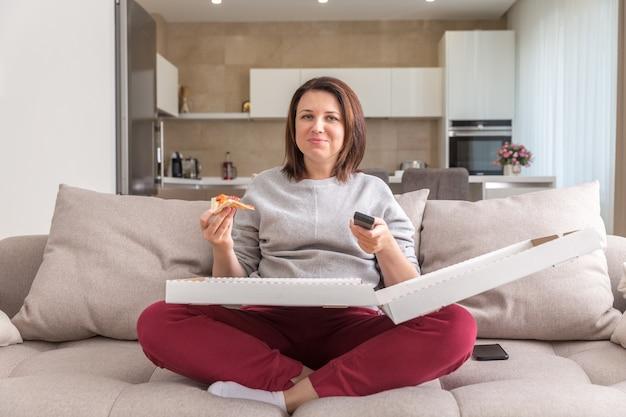 Ragazza che mangia pizza che si siede sullo strato e che guarda tv in appartamento moderno