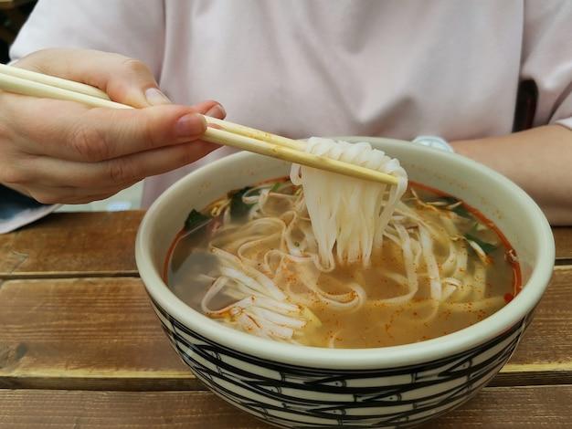 Ragazza che mangia spaghetti di riso con le bacchette in un caffè di strada.