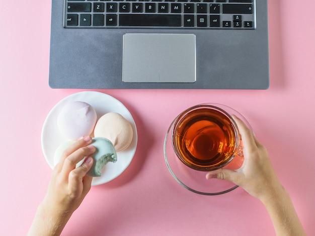 La ragazza mangia un marshmallow blu con tè davanti al computer su un tavolo rosa. la vista dall'alto.