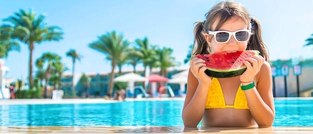 La ragazza mangia l'anguria dentro la piscina