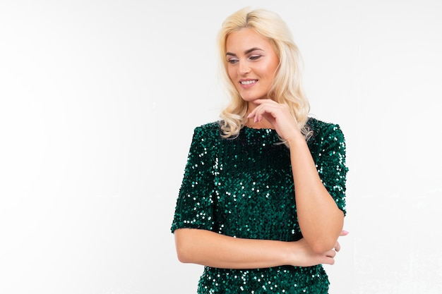 Ragazza in elegante abito verde lucido fa uno sguardo pensieroso su uno sfondo bianco studio