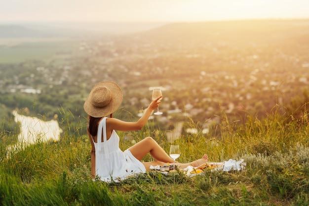 Ragazza in abito bianco elegante e cappello di paglia con picnic romantico in montagna con il fiume