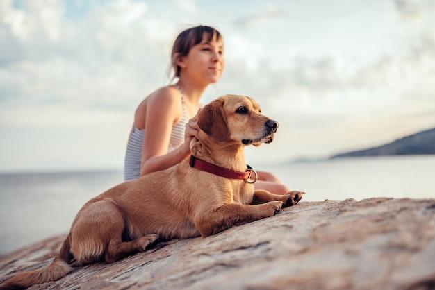 Ragazza che abbraccia il suo cane mentre era seduto sulla roccia in riva al mare