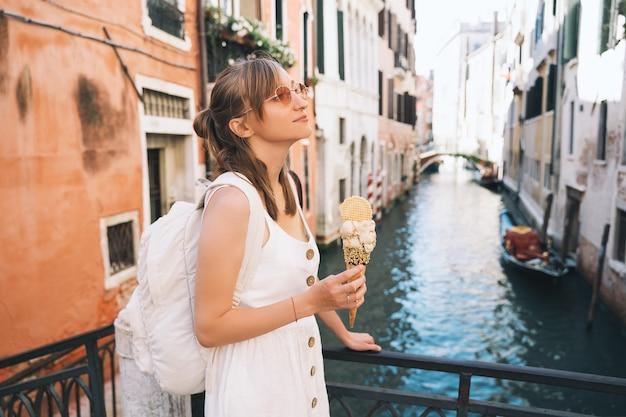 La ragazza gode del bellissimo e delizioso gelato italiano nel cono di cialda sui ponti panoramici di venezia