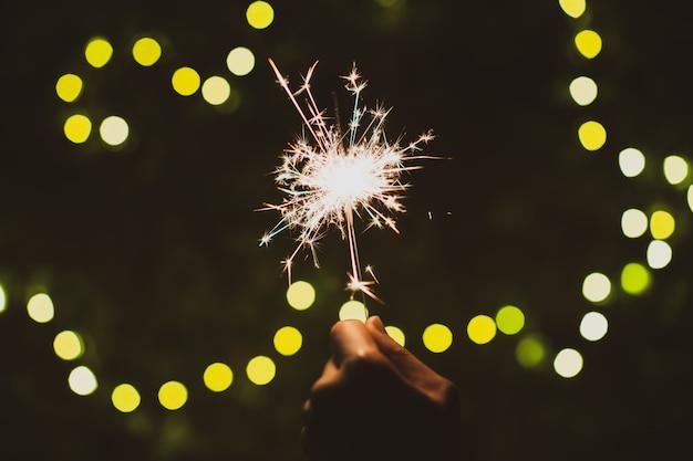 La ragazza si diverte a giocare a piccoli fuochi d'artificio a mano scintillante, celebrando nel festival di natale e capodanno.