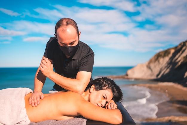Ragazza che gode nel massaggio sulla costa vicino al mare, massaggiatrice con maschera facciale nella pandemia di coronavirus