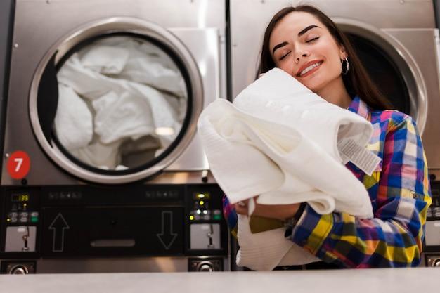 La ragazza gode di asciugamani puliti e profumati dopo il lavaggio in lavanderia