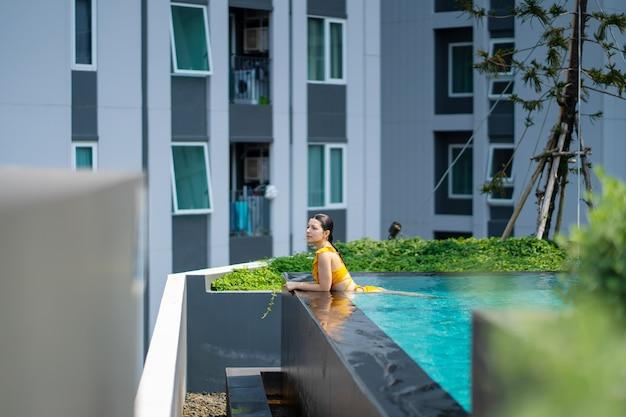 La ragazza si diverte a rilassarsi in piscina in una calda giornata estiva. piscina in un complesso residenziale cittadino.